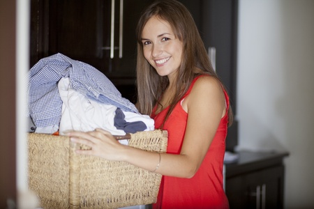 laundry room: Cute young woman carrying a basket with clothes