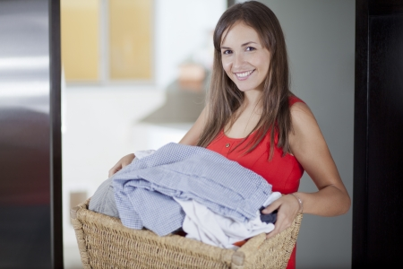 Cute young housewife washing some clothes at home Stock Photo