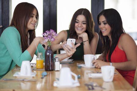woman on phone: Beautiful female friends having fun at a restaurant  Stock Photo