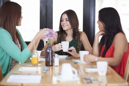 coffee table: Cute female friends hanging out in a restaurant