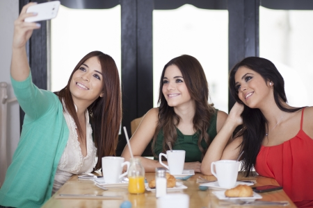 best coffee: Female friends taking their photo with a cell phone