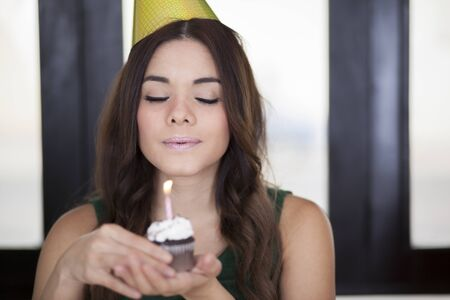 Beautiful young woman making a wish on her birthday photo
