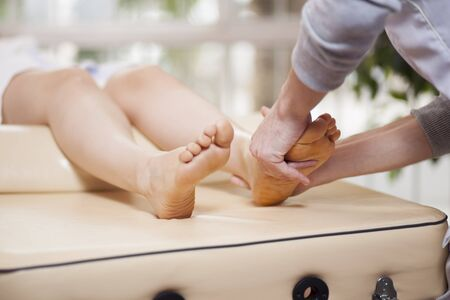 Masseuse giving a foot massage to a female customer photo