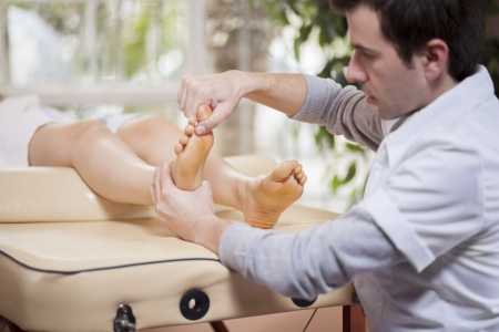 muscle tension: Young masseuse giving a foot massage to a client