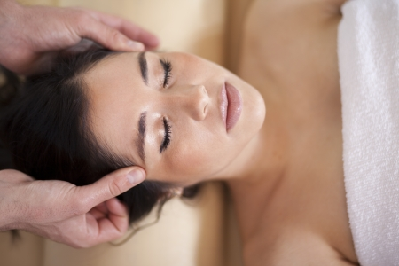 Gorgeous young woman getting a head massage at a spa photo
