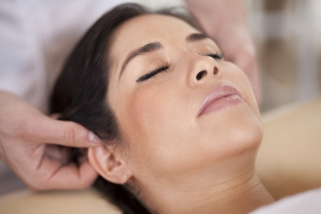 Beautiful chubby woman getting an ear massage at a spa photo