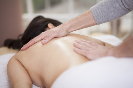 massage oil: Chubby woman getting a massage at a health and beauty spa