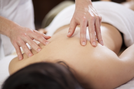 pain relief: Closeup of a young woman getting a back massage at a spa