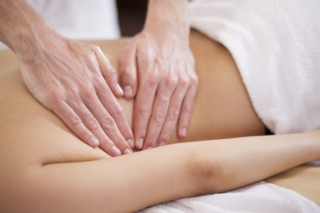 Closeup of the hands of a therapist giving a back massage photo