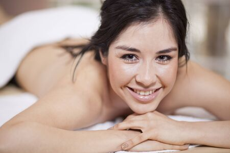 Happy young woman loving her massage at home photo