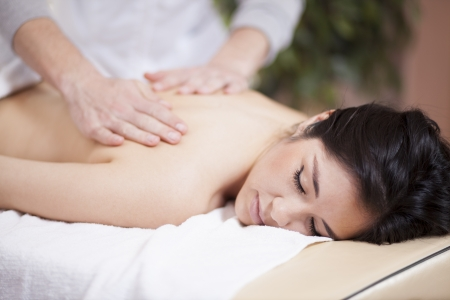 back ache: Cute young woman getting a back massage at a spa