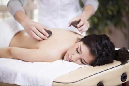 Very relaxed young woman getting a stone massage at a spa photo