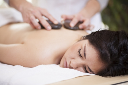 Pretty woman getting a hot stone massage at home photo