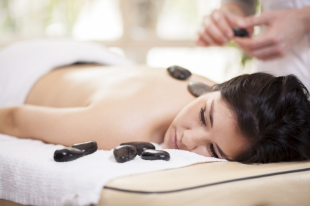 Male therapist applying some heat with hot stones during a massage photo