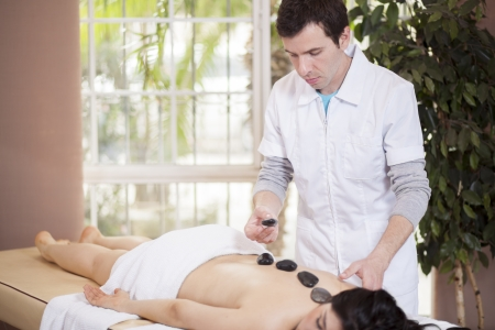 Young male therapist giving a stone massage to a customer photo
