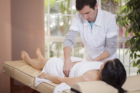Male therapist giving a massage to a customer at a spa photo