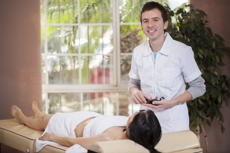 Young male therapist about to give a stone massage to a female customer photo