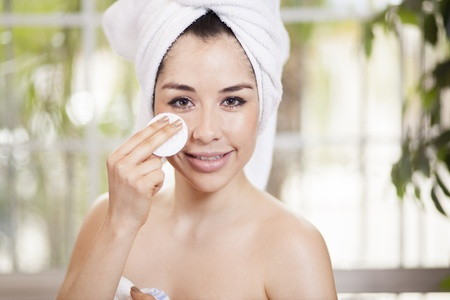 Cute young woman cleaning her face with a cotton pad photo