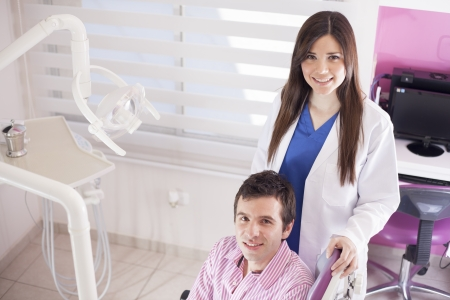 Beautiful young dentist and a patient at the dental office photo