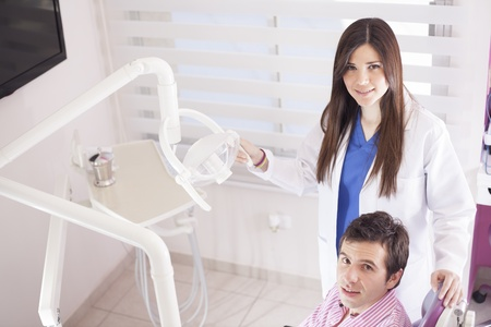 Happy female dentist working on a patient photo