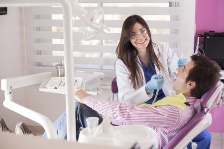 oral surgery: Beautiful female dentist working on a patient