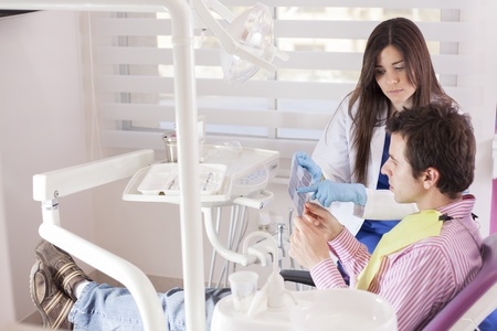 Young female dentist showing some x-rays to a patient photo