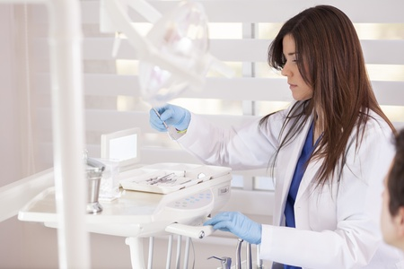 surgical coat: Cute female dentist grabbing an instrument from a tray