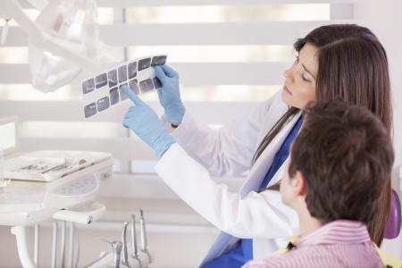 Carino dentista che mostra i raggi X per un paziente Archivio Fotografico