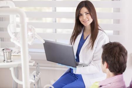 denti: Dentista feliz hembra de verificar el archivo de un paciente en su computadora port�til