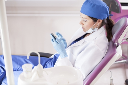 Young female dentist sending a text message at the dental office Stock Photo - 18269380