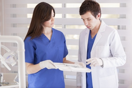 Dentist and assistant choosing the right instrument photo