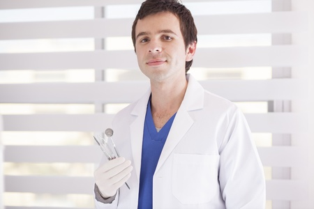 male dentist: Young handsome dentist holding some of his instruments Stock Photo
