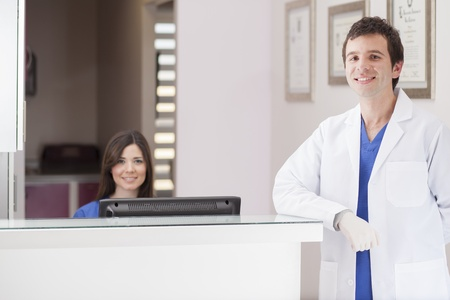Male dentist and assistant greeting patients at the front desk Stok Fotoğraf