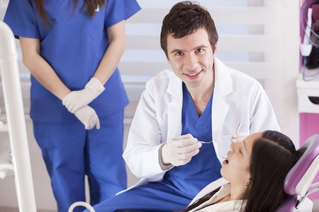 Handsome young dentist working on a patient photo