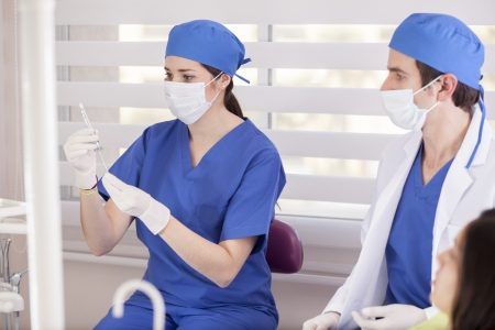 Assistant preparing a shot of anesthesia for a patient Stock Photo - 18269347