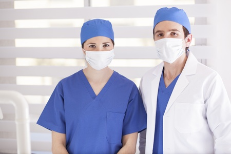 Couple of young doctors wearing face masks and ready to operate photo