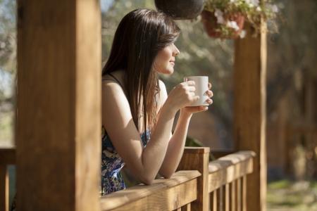 mujer tomando cafe: Chica linda ver como el sol se levanta desde la cubierta de una caba�a de troncos s