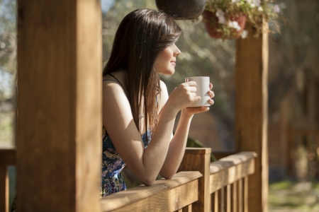 coffee cups: Cute girl seeing how the sun rises from a log cabin s deck Stock Photo