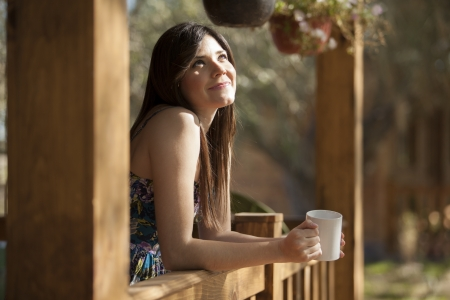 hush hush: Cute young woman having a cup of coffee on a log cabin s deck Stock Photo