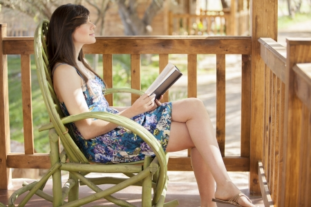novel: Gorgeous young woman sitting on a log cabin s deck and reading a book Stock Photo