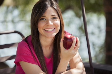 Cute young woman eating an apple and smiling Stock Photo - 18321028