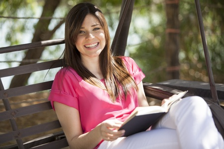 Happy young woman reading a book and relaxing outdoors Stock Photo - 18321032