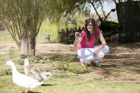 Cute girl taking some pictures of ducks in a  farm photo