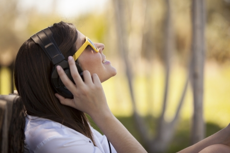 Cute woman listening to some music and looking towards copy space photo