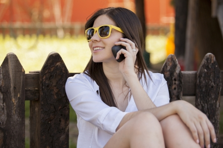 Beautiful girl relaxing at the park while calling a friend on her cell phone photo