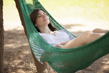 resting: Very relaxed woman sleeping in a hammock outdoors
