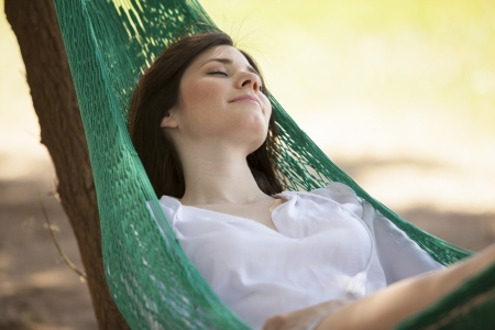 Happy woman relaxing in a hammock during her outdoor vacation photo