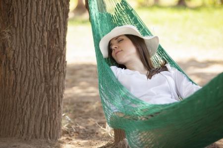 屋外のハンモックで昼寝をして豪華な若い女性 写真素材