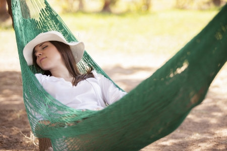Pretty girl relaxing and taking a nap in a hammock during vacation Imagens