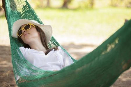 Cute young woman relaxing in a hammock outdoors photo